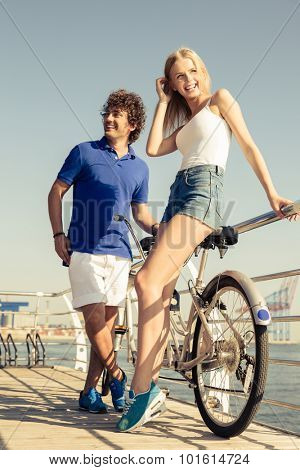 Portrait of a cheerful couple with tandem bicycle resting outdoors