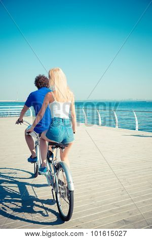 Portrait of a man and woman riding in tandem bicycle outdoors