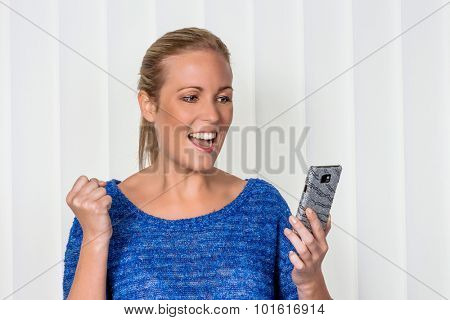 a young woman enjoying a sms she received on her phone.