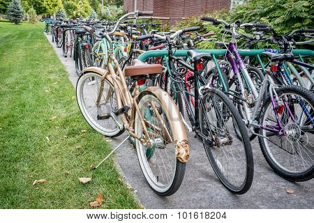 FORT COLLINS, CO - SEPTEMBER 14, 2015: A variety of  bicycles parked on  racks at a campus of Colorado State University. Bikes are popular way of commuting among students and staff.