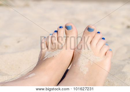Closeup On Woman Sandy Feet With Blue Nails Pedicure Under Sunlight