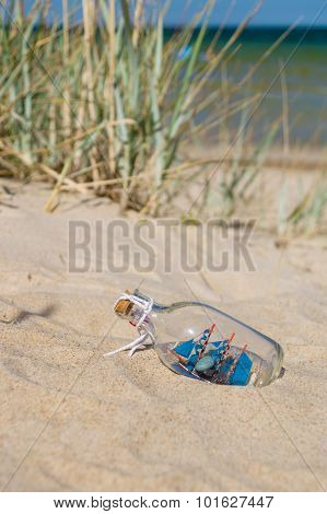 Small Ship In The Glass Bottle Lying On The Beach, Souvenir Concept