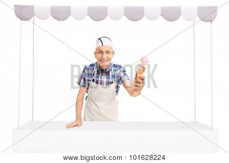 Senior ice cream vendor standing behind a stall and giving an ice cream towards the camera isolated on white background