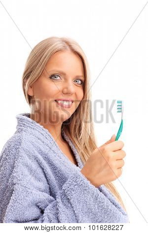 Beautiful blond woman in a blue bathrobe holding a toothbrush and looking at the camera isolated on white background