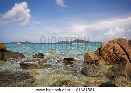 Tropical beach with small stones and waves on the foreground