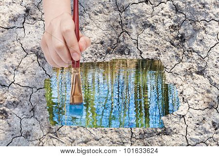 Paintbrush Paints Water Puddle On Dried Earth