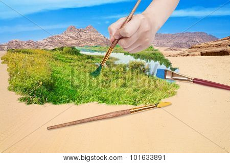 Hand With Paintbrush Paints Green Meadow In Desert