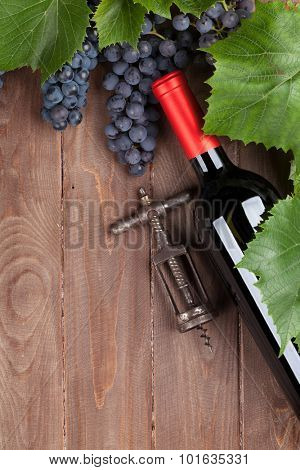 Red grape, wine bottle and vintage corkscrew on wooden table. Top view with copy space