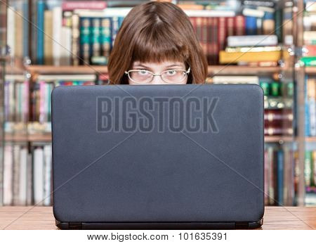 Girl Looks Over Cover Of Laptop In Library