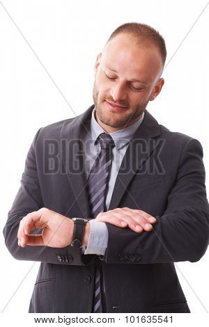 Businessman checking time on wristwatch, standing over white background.