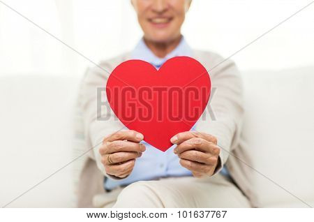 age, holidays, valentines day, love and people concept - close up of happy smiling senior woman with red heart shape at home