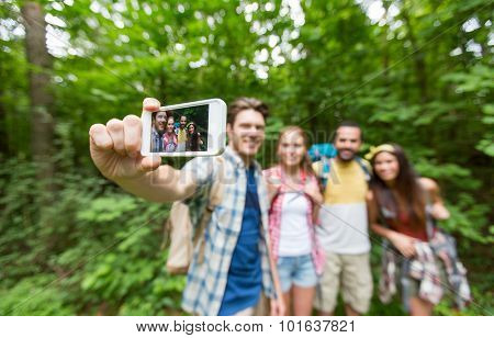 technology, travel, tourism, hike and people concept - close up of happy friends walking with backpacks taking selfie by smartphone in woods