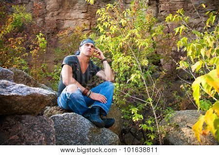 Man Rests In The Nature Sitting On A Stone