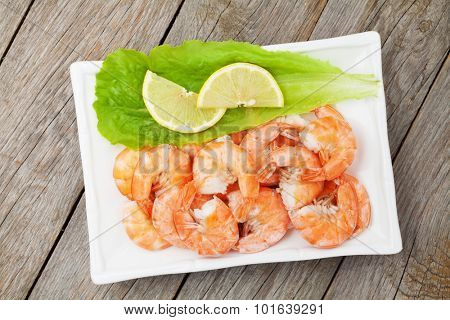 Cooked shrimps with lemon and salad leaves. View from above on wooden table