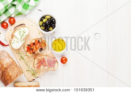 Bruschetta with cheese, tomatoes and prosciutto on cutting board. Top view with copy space