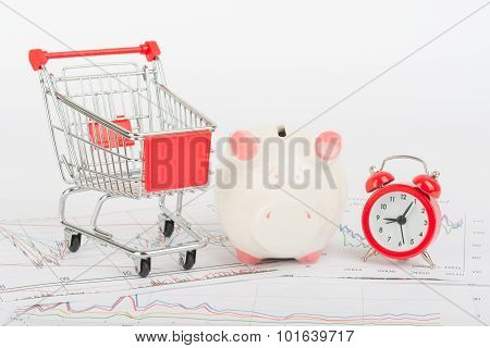 Shopping cart with piggy bank and clock