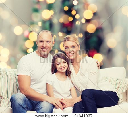 family, childhood, holidays and people concept - smiling mother, father and little girl over christmas tree lights background
