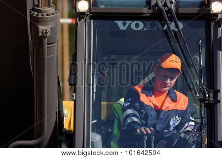 NOVOPRIOZERSK HIGHWAY, LENINGRAD OBLAST, RUSSIA - SEPTEMBER 11, 2015: Participant of grader competitions during the final of Worldskills Russia championship among road workers