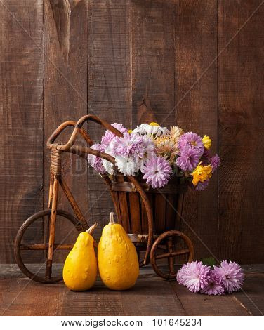 Autumn still life -  Two decorative pumpkins and   chrysanthemums bunch against the background of old wooden wall.