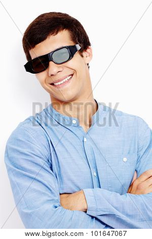 Close up portrait of young hispanic man wearing jeans shirt and 3D TV LCD shutter glasses standing with crossed arms and smiling against white wall - 3D film concept