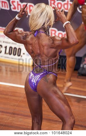 Female Bodybuilder In Back Double Biceps Pose On Stage