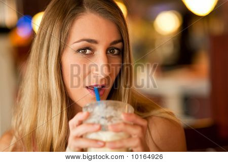 Woman in restaurant drinking milkshake