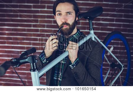 Portrait of smart man with bicycle smoking pipe against brick wall