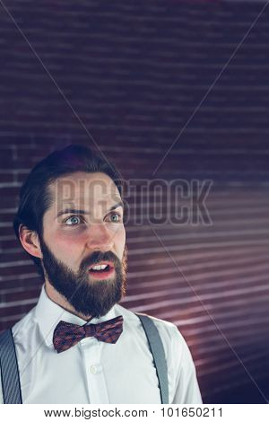 Confused hipster looking away against brick wall
