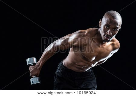 Portrait of muscular man bending while exercising against black background