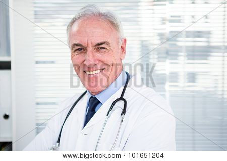 Portrait of happy doctor with stethoscope around his neck at clinic