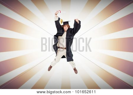 Male student in graduate robe jumping against linear design