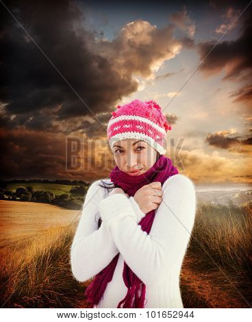 Attractive woman wearing warm clothes against country scene