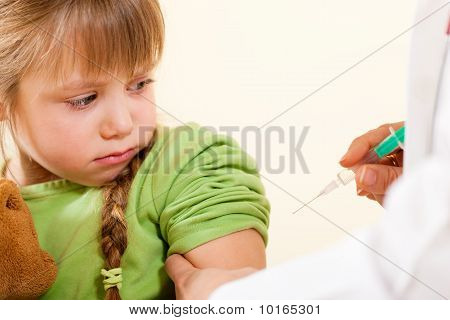 doctor applying syringe to child - Pediatrician