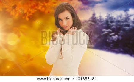 Brunette in white jumper smiling at camera against autumn changing to winter