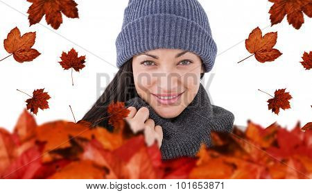 Attractive brunette looking at camera wearing warm clothes against autumn leaves