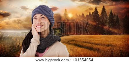 Attractive brunette looking up wearing warm clothes against country scene