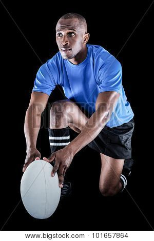 Rugby player holding ball while kneeling on black background