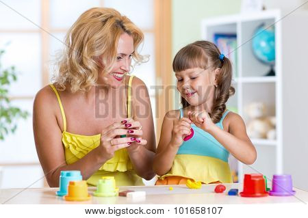 Mother and kid playing plasticine at home