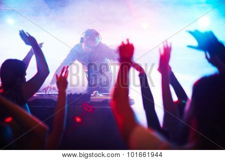 Energetic deejay standing by turntables in front of dancing crowd