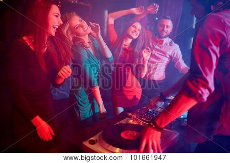 Cute girls dancing by turntables and dj adjusting sound