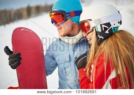 Amorous snowboarders in winter activewear spending vacation at sportive resort