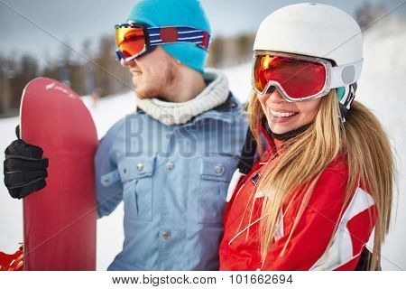 Pretty female snowboarder in winter activewear looking at camera during vacation at sportive resort with her boyfriend near by