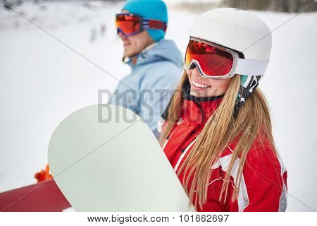 Happy young snowboarder in activewear looking at camera on background of her boyfriend on winter resort