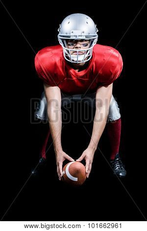 American football player bending while holding ball against black background