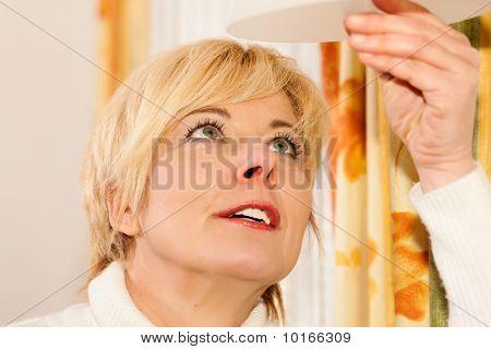 Woman changing a light bulb