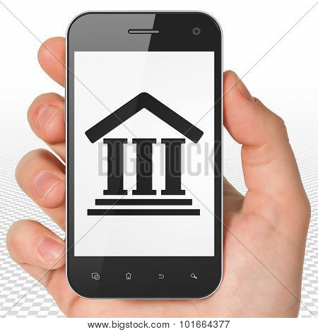 Law concept: Hand Holding Smartphone with Courthouse on display