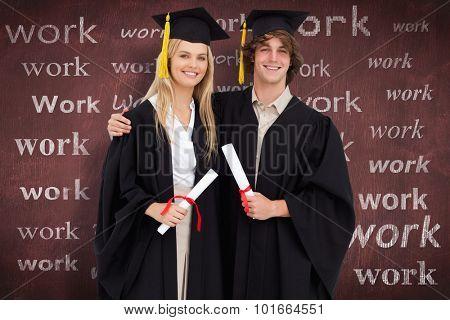 Two students in graduate robe shoulder to shoulder against desk