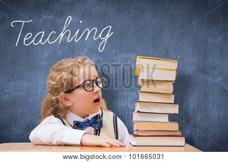 The word teaching and surprise pupil looking at books against blue chalkboard