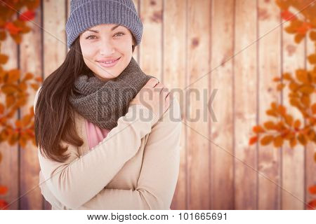 Attractive brunette looking at camera wearing warm clothes against autumn leaves pattern