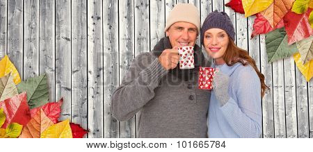 Happy couple in warm clothing holding mugs against digitally generated grey wooden planks